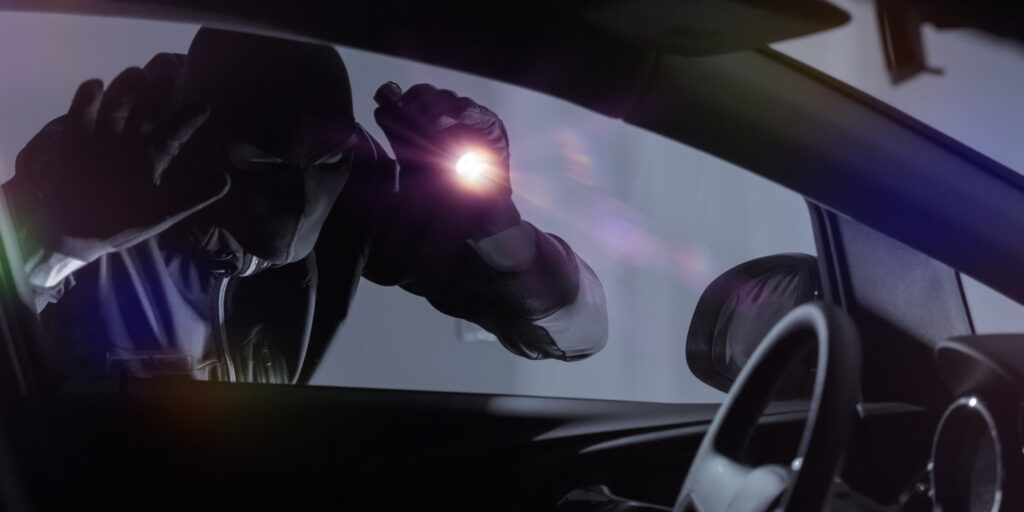 Car Robber with Flashlight Looking Inside the Car