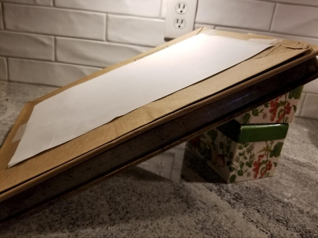 Newsprint on the cardboard angle adjuster, propped up on recipe boxes